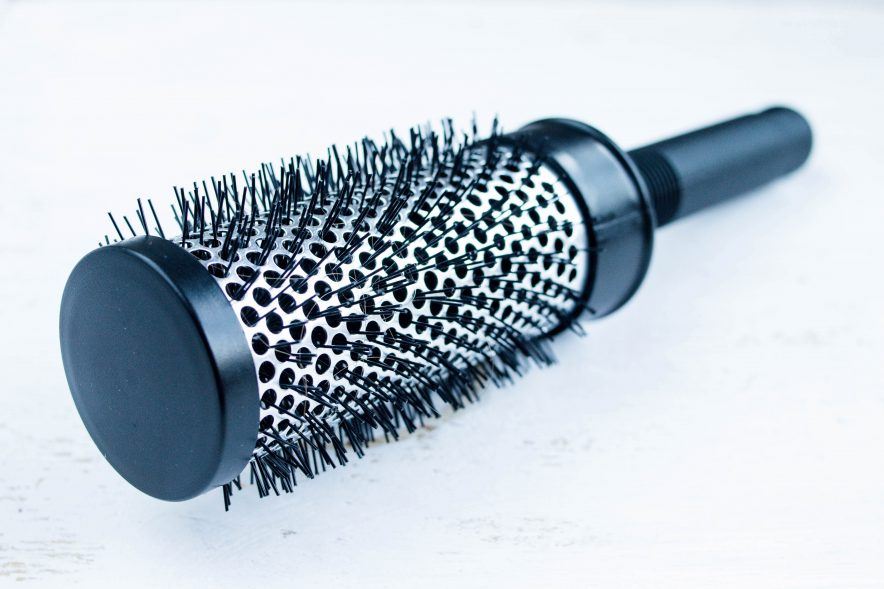 A black, rounded hair brush with synthetic bristles