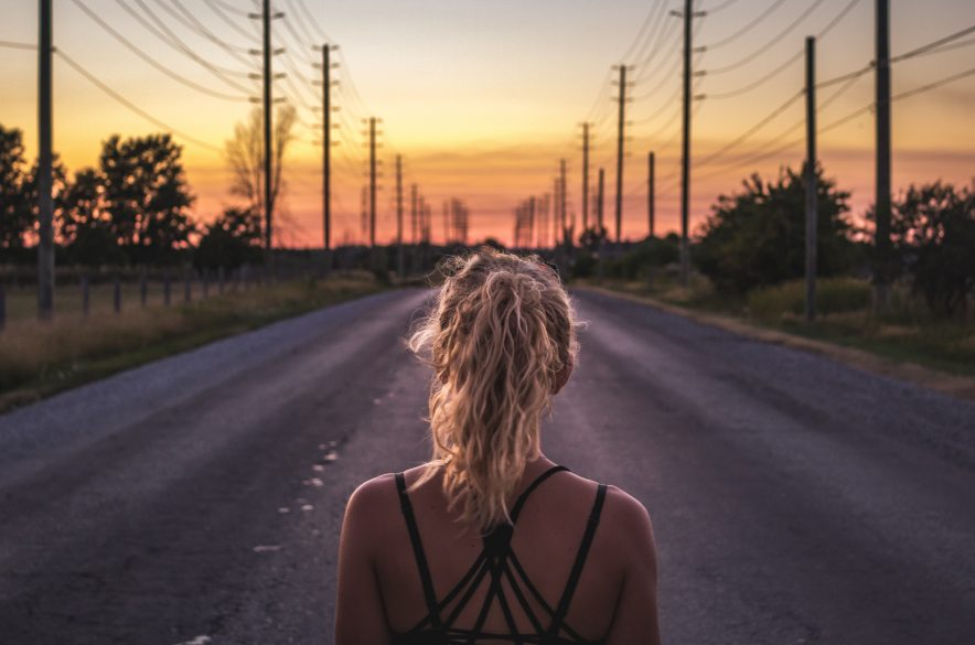 A girl standing on a road watching the sunset